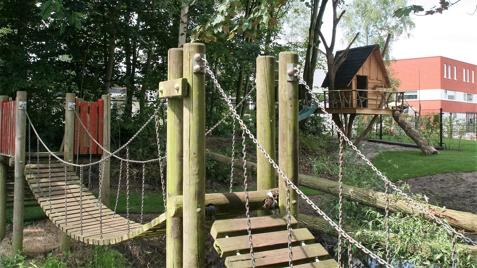 Tuin met hangbrug en boomhut